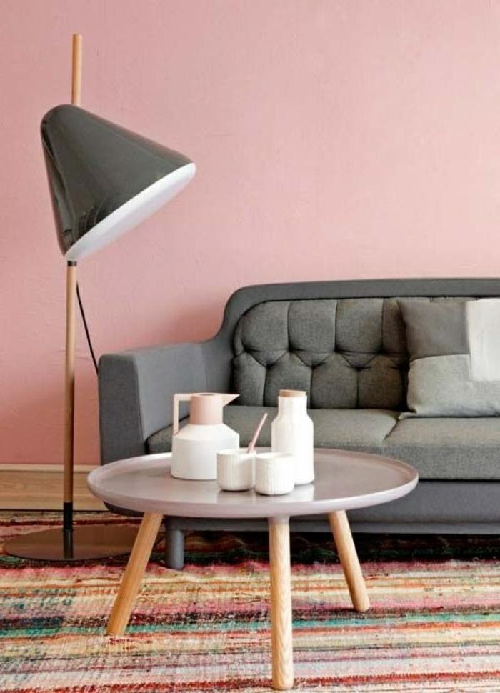 Minimalistische Ausstattung eines Wohnzimmers in moderne Farben, bunter Teppich und runder Tisch, Wohnzimmer grau rosa, große Lampe