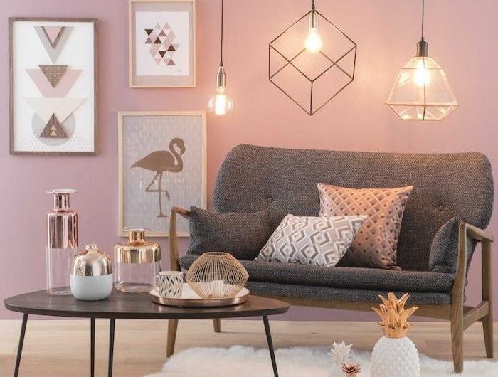 Wohnzimmer grau rosa modern eingerichtet, kleines Sofa in grau mit pinken Kissen, Bilder an die mit geometrischen Motiven, drei Pendelleuchte