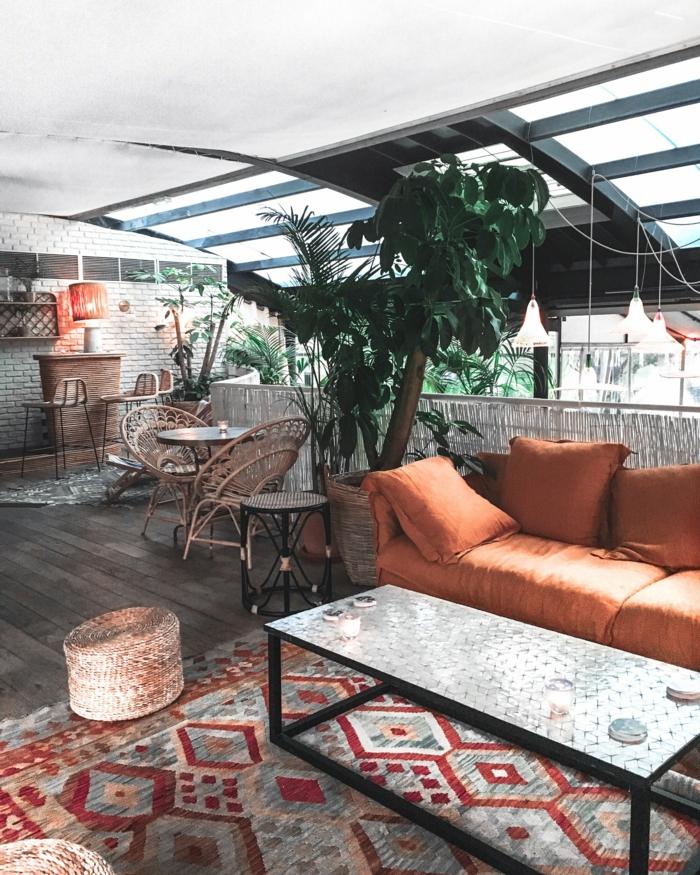 Bohemisches Wohnzimmer mit große grüne Pflanze, Sofa in Orange, bunter geometrischer Teppich