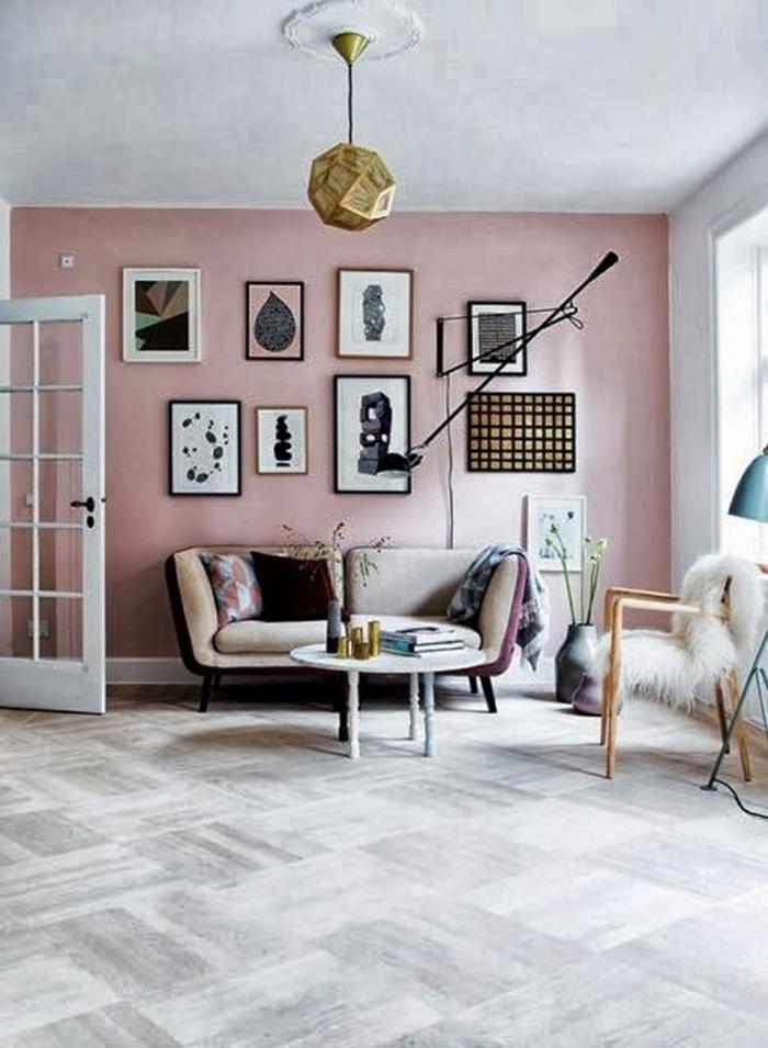 Wohnzimmer grau rosa, Wandfarbe Inspiration, große Wand mit aufgehängten Bildern, kleiner Couch in beige, Stuhl mit flauschiger Decke