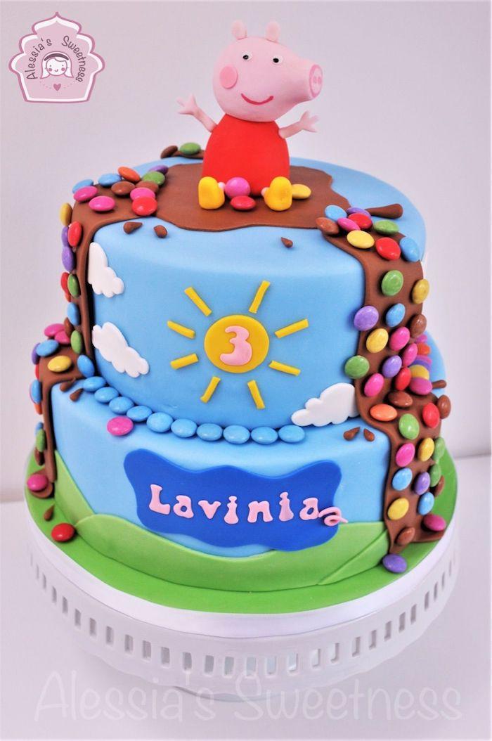 Zweistöckige blaue Fondanttorte, Peppa Wutz Figur auf der Torte, bunte Bonbons, Sonne und Wolken