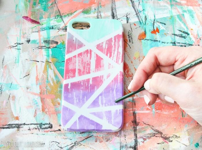 Bunte Handyhülle selbst gestalten in pink, lila und blassgrün, Hand malt vertikale Streifen, bunter Hintergrund