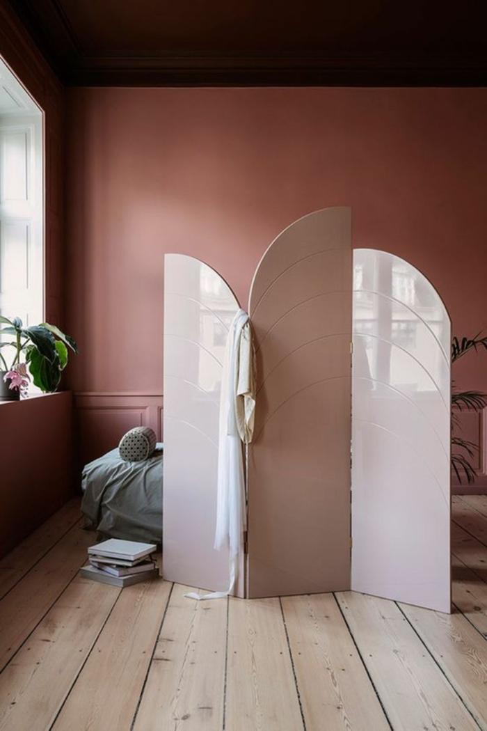 Wohnzimmer Wandfarbe Inspiration in altrosa, spanische Wand aus Glas die ein Bett mit grünen Bettwäschen versteckt