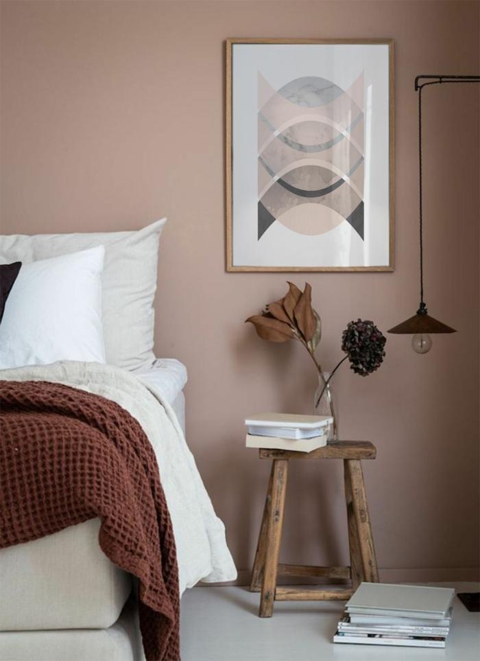 Schlafzimmer altrosa mit einem Bild in Pastelltöne, kleiner Tisch aus Holz mit Büchern und Blumen obendrauf, schwarze hängende Lampe,