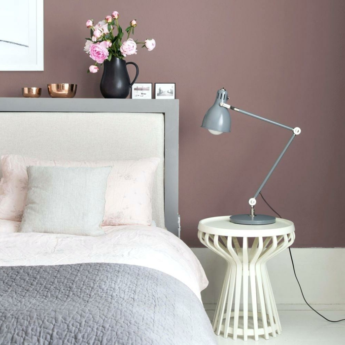 Schlafzimmer altrosa mit grauen Bettwäschen, weißer Tisch mit grauer Lampe obendrauf, schwarze Vase mit rosa Blumen