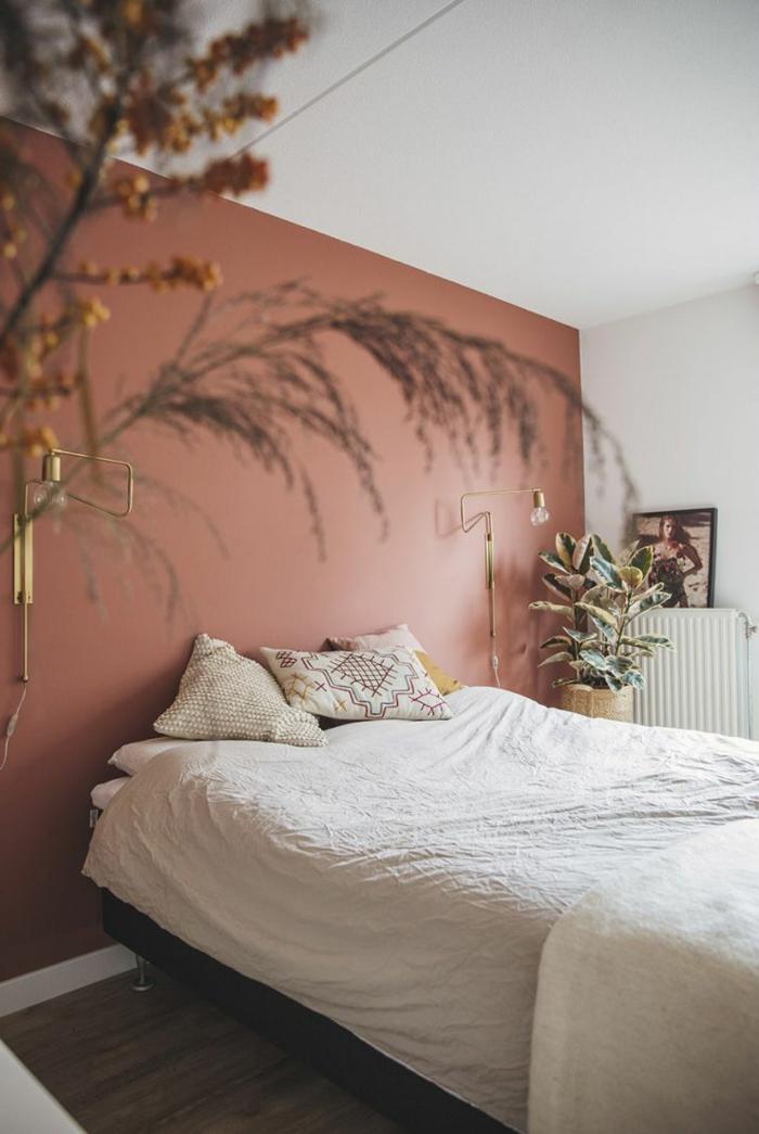 Schlafzimmer altrosa mit einer bemalten Wand in dieser Farbe, Bett mit weißen Bettwäschen und Kissen, Pflanzen als Dekoration