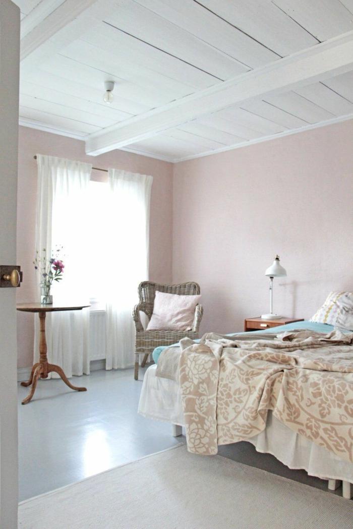 Elegantes Schlafzimmer in pastell rosa Wandfarbe, großes Bett mit hellen Bettwäschen, großer Korbstuhl, runder Tisch aus Holz
