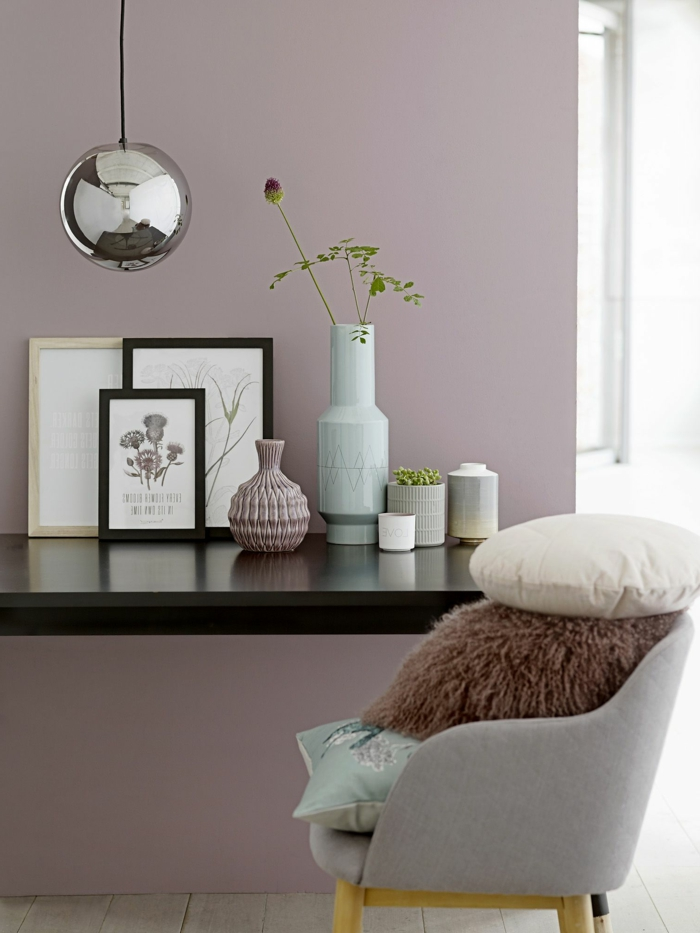 Schlafzimmer altrosa, Stuhl in grau mit Kissen in weiß und braun, schwarzer Tisch mit Bildern obendrauf, Wandfarbe altrosa