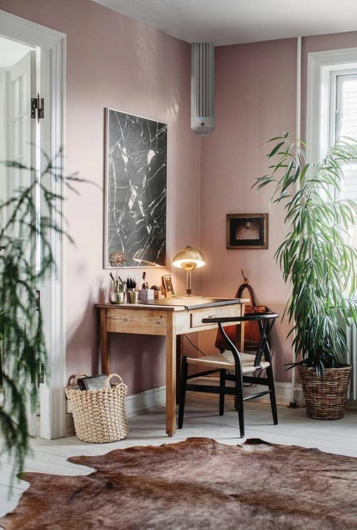 Schlafzimmer altrosa, Schreibtisch aus Holz, schwarzes Gemälde auf Wand in rosa Farbe, brauner Teppich, grüne Pflanzen