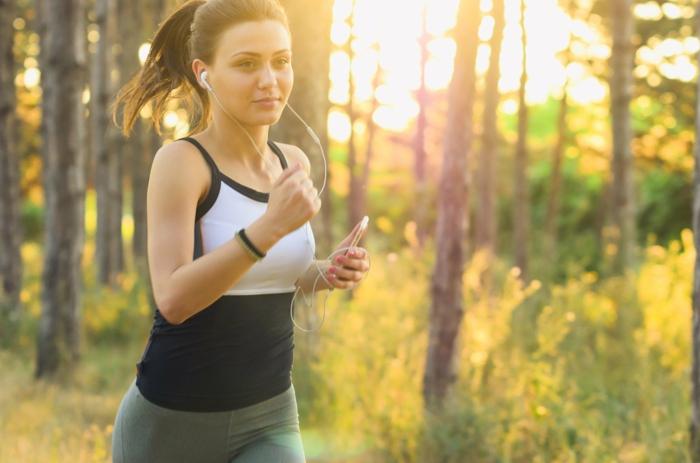 Gesund leben, Frau rennt im Park am sonnigen Tag, Handy in Hand, aufgesetzte Kopfhörer, grüne Leggings, schwarz weißes Top