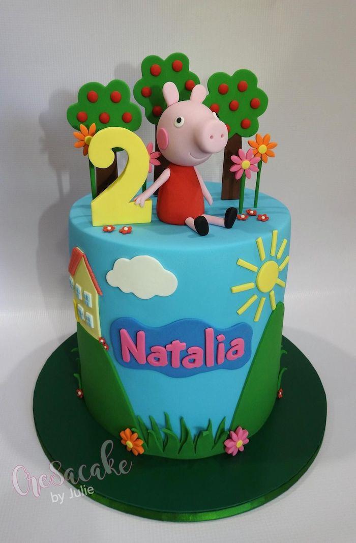 Blaue Torte mit Fondant Figur Peppa Wutz, Apfelbäume und Blumen für zweiten Geburtstag