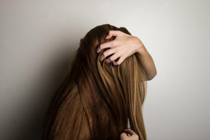 Braune glatte lange Haare, Traumfrisuren zaubern mit dem Glätteisen, Hand einer Frau im Haar