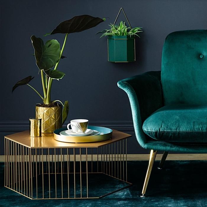 trendfarben 2020, dunkelblaue wand, desginer sessel in smaragdgrün, metallene elemente, wohnzimmerdeko