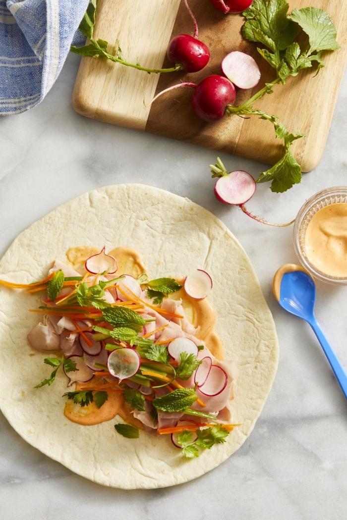 vegetarische wraps mit gemüse und creme soße, geshcnittene radieschen, kräutern