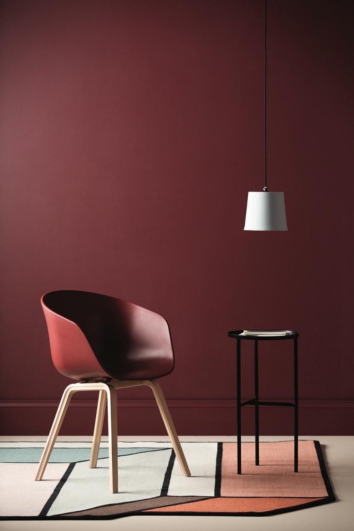 wandfarbe beere, desginer stuhl, teppich mit geometrischen motiven, weiße lampe, runder tisch