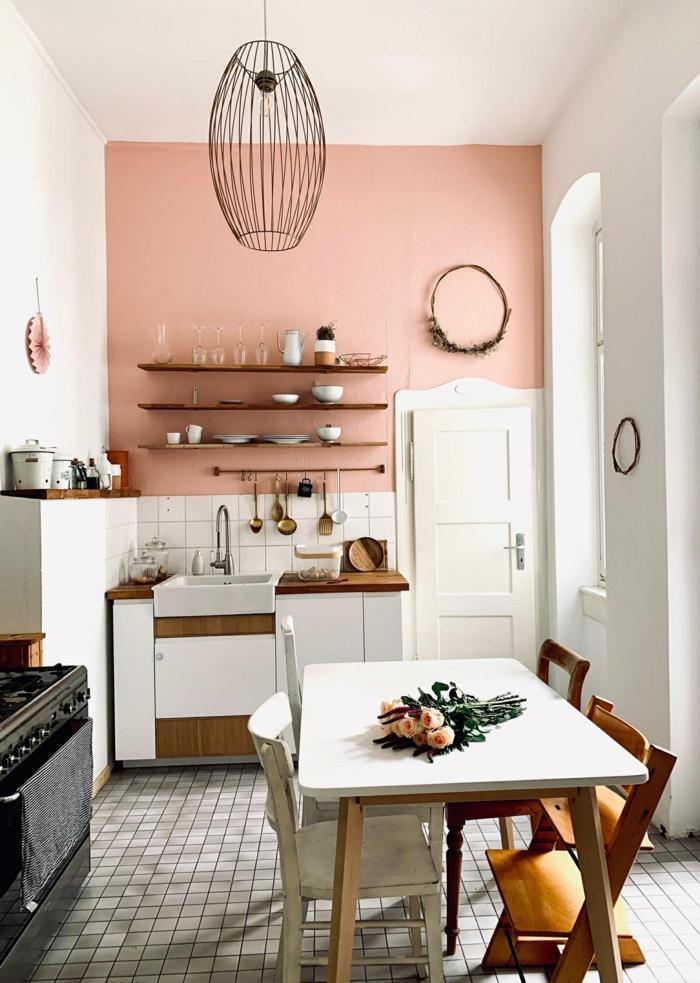 Wandfarbe Inspiration altrosa für kleine Küche, Ofen in schwarzer Farbe, weißer rechteckiger Tisch, attraktive Pendelleuchte, hängender Kranz über die Tür