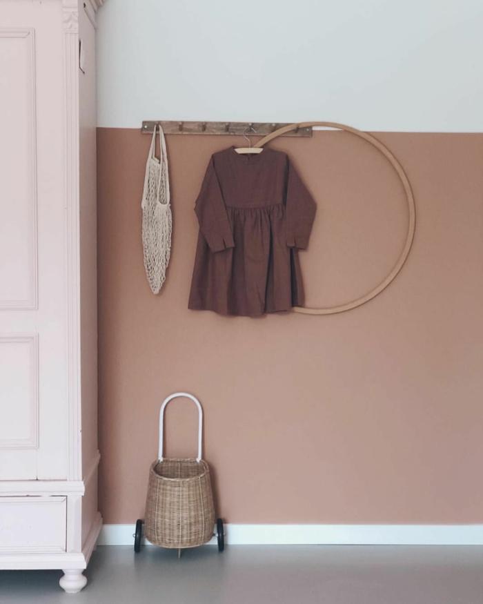 Farben für Wohnzimmer tipps,Wandfarbe altrosa, aufgehängtes Kleid in ziegelrot, Hula Hoop Reifen in braun, Weidenkorb mit Räder