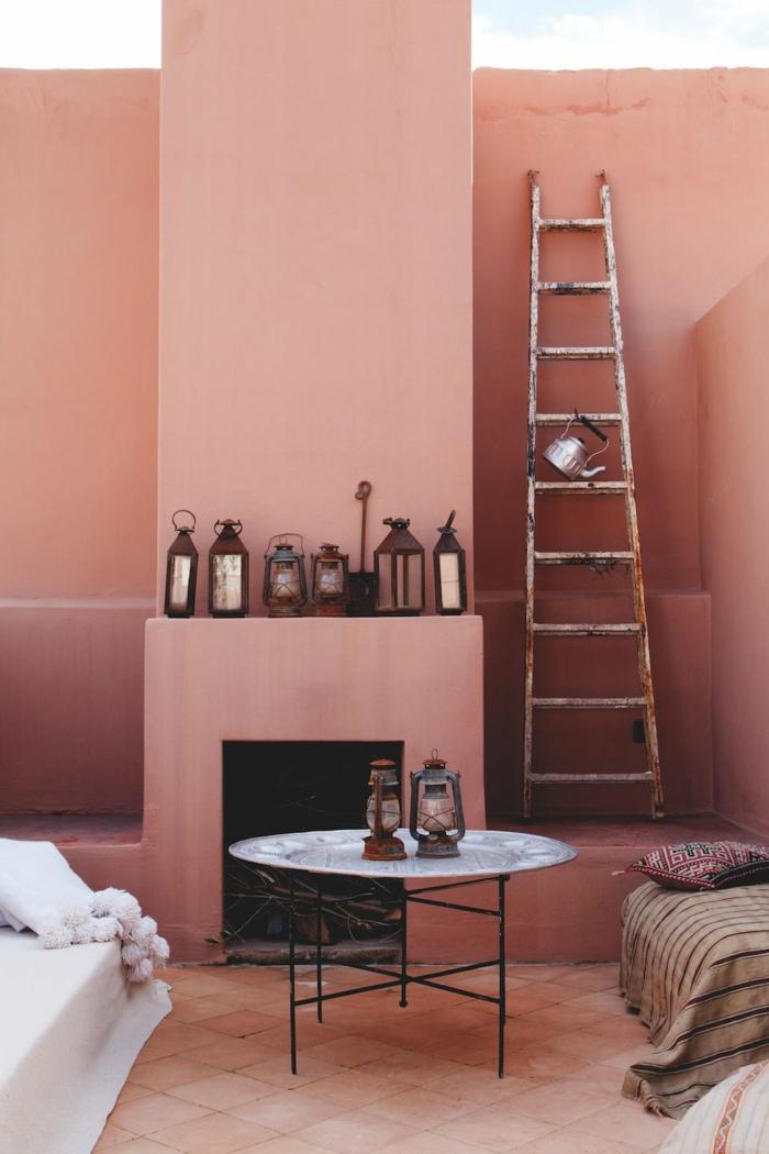 viele Laternen als Dekoration, eine Leiter, runder Tisch mit dünnen Beinen, weißer Couch, pastell rosa Wandfarbe