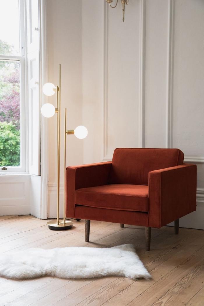 wohnzimmer farben 2019, oranger sessel, flauschiger teppich, boden aus holz, goldene stehlampe