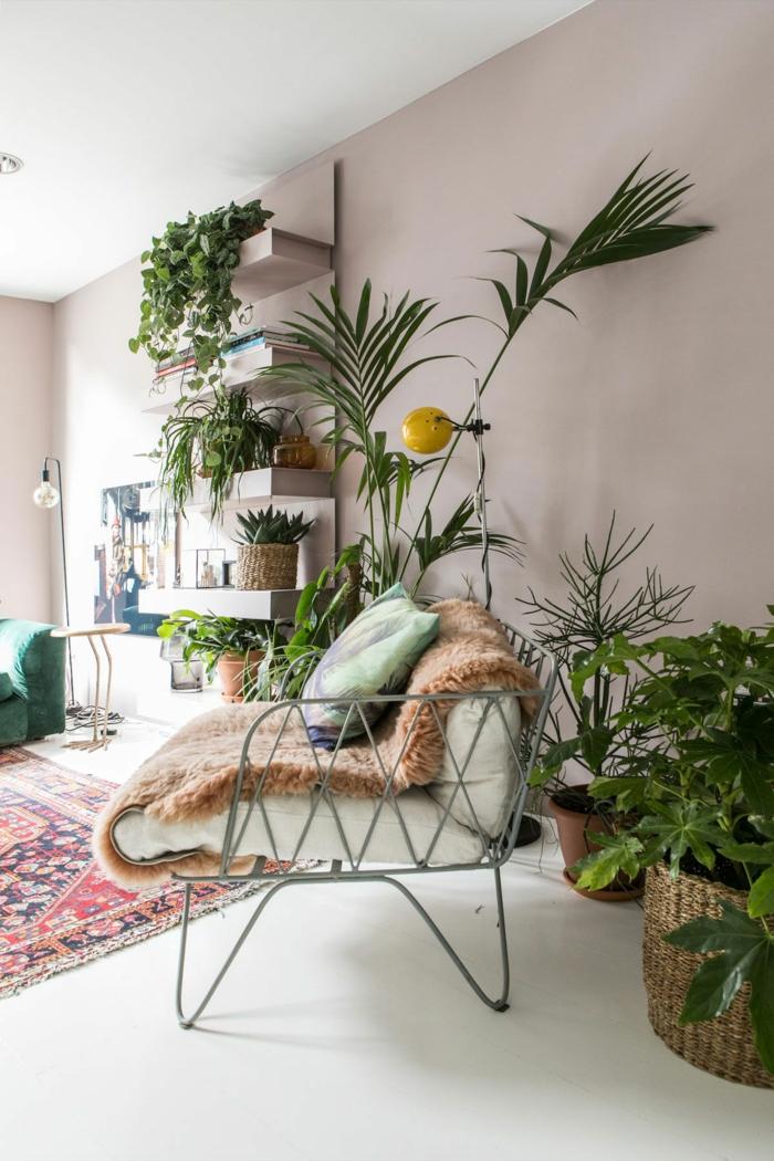 Dekoration mit vielen grünen Pflanzen, Wohnzimmer altrosa, Farbe für Wand, bunter Teppich mir roten Schattierungen, Couch und Kissen in grün