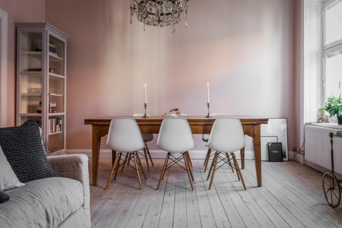 Wohnzimmer mit Esszimmer in wandfarbe altrosa, Holztisch und Stühle in weißer Farbe, großes Couch in grau,