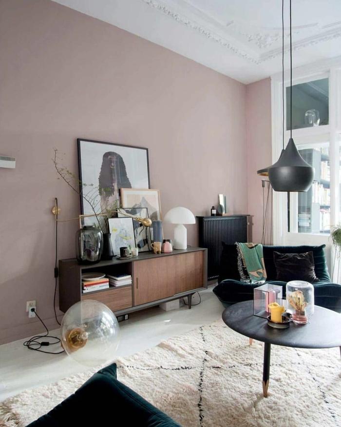 Farbe für Wand altrosa, moderne Ausstattung, weißer Teppich und schwarzer runder Tisch, Sessel in grün