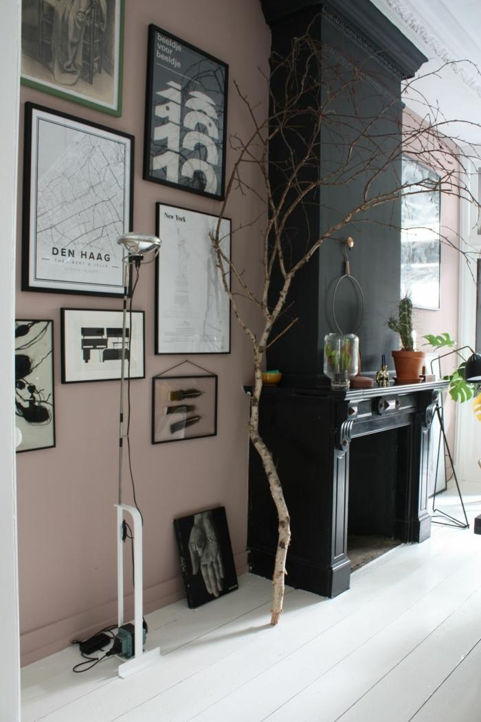 Wohnzimmer Einrichtung mit Kamin in schwarz, Farbe für Wand altrosa, Galleriewand mit schwarz weiße Bilder, dekorativer Baum,