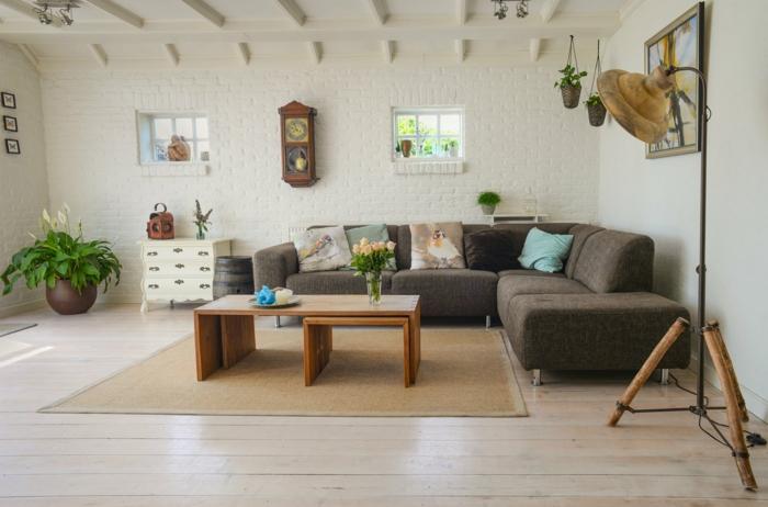 Interior Design 2020 Trends, Japandi Style, Wohnzimmer mit Ecksofa in grau, Ziegelwand in weiß, grüne Pflanzen