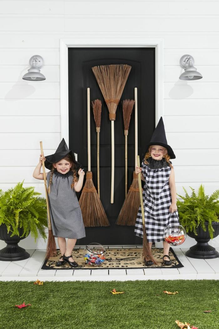 Hexenkostüme von zwei Mädchen in schwarze Kleider, schwarze Hütte und Besen, kinder faschingskostüme
