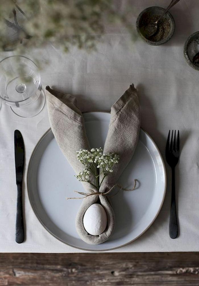 Gefaltene Serviette in Form von Hasenohren mit einem weißen Ei in der Mitte, Osterdeko selber machen, minimalistische Tischdekoration