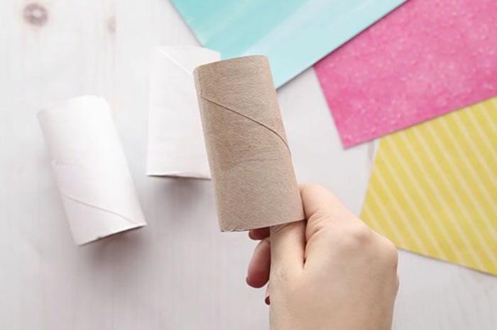 Klopapierrolle bemalen in weißer Farbe, Osterhasen selber basteln, DIY Ideen, pinterest osterdeko, Hand hält eine Rolle