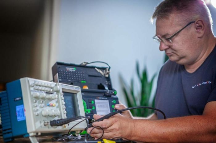 Was heißt DGUV 3, elektrische Sicherheitsprüfung, Mann mit Brillen prüft ein elektrisches Gerät