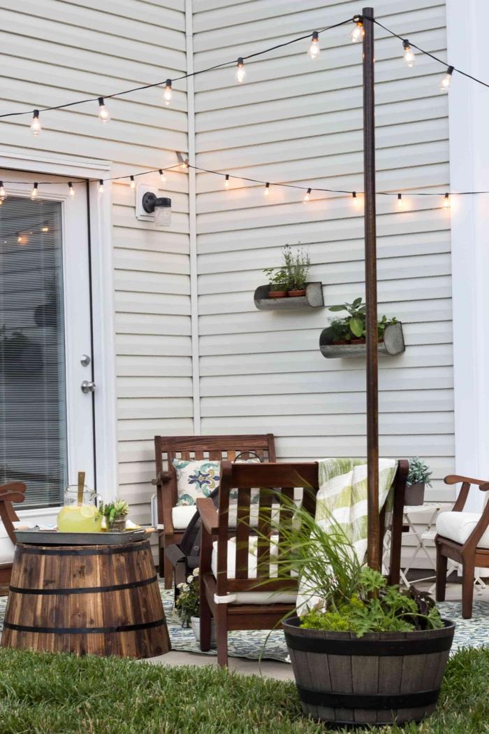Dekoration mit aufgehängten kleinen Lichterketten, Stühle aus Holz, Ideen Gartengestaltung, großer Blumentopf mit Pflanze