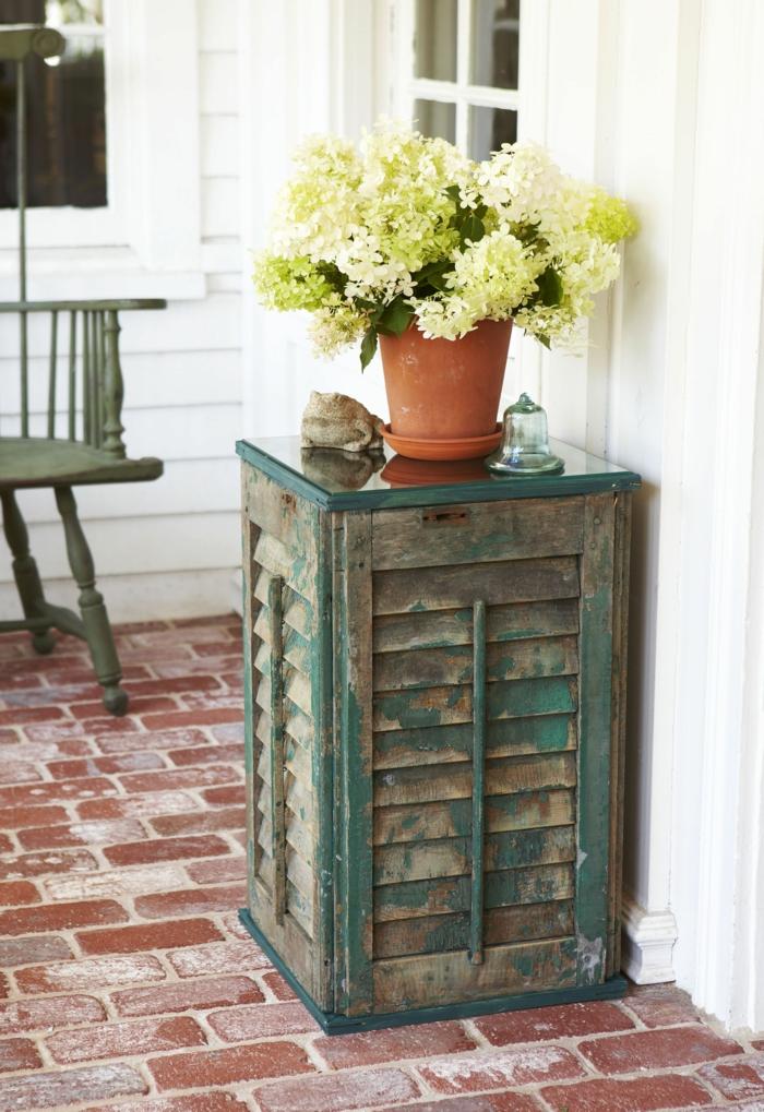 Upcycling Ideen Garten, Tisch aus alten grünen Jalousien, Gartendeko selber machen, Blumentopf mit gelben Blumen