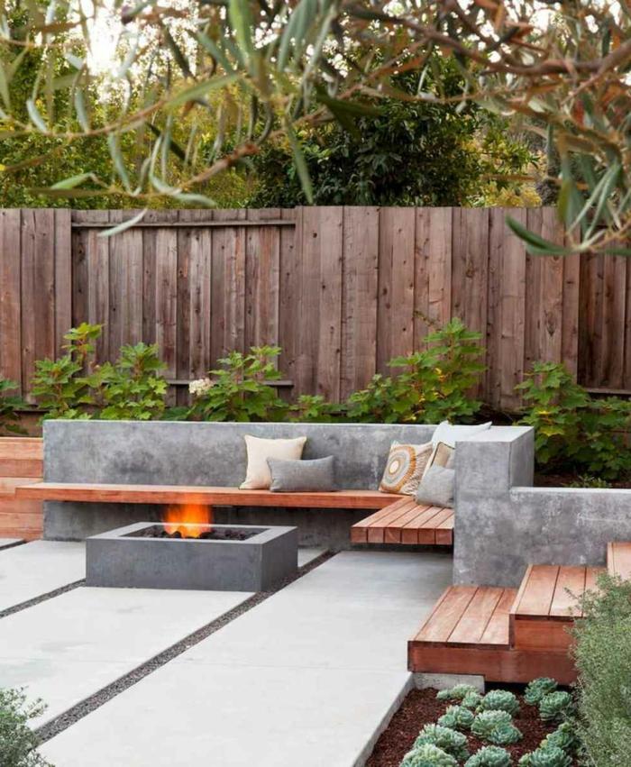 beton ideen für den Garten, Sitzbereich mit Holzbank und Kissen, gartendeko ideen, Feuerstelle aus Beton, Sichscutz aus Holz