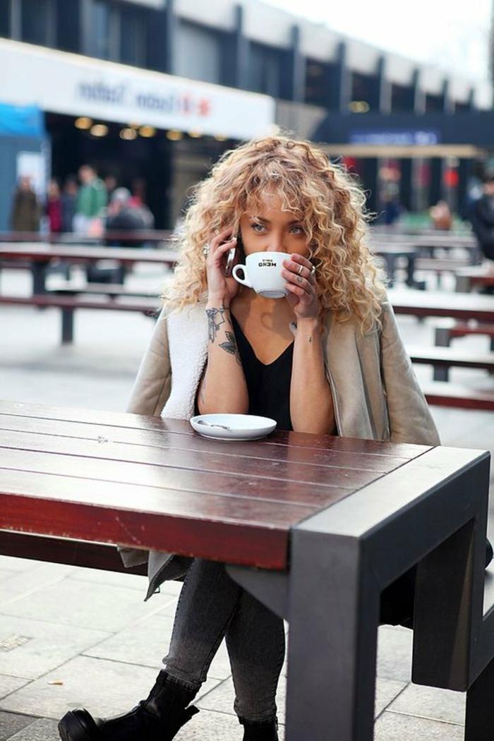 Frau mit blonden Haaren trinkt Kaffee draußen, Tattoo auf der Hand, Kurzhaarfrisuren mit Locken, beige Jacke