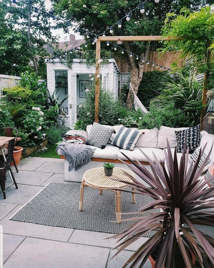 Gestaltun eines Gartens mit vieleb grünen Pflanzen, Ecksofa mit Kissen, Gartengestaltung Ideen, kleiner runder Tisch