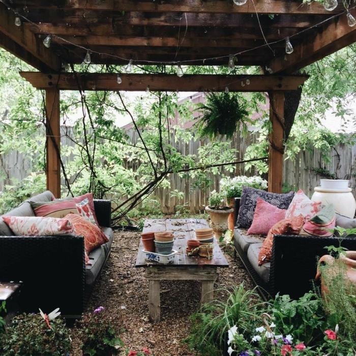 Gartengestaltung im bohemischen Stil mit vielen bunten Kissen, aufgehängte Lichtketten, gartendeko ideen, großer Holztisch