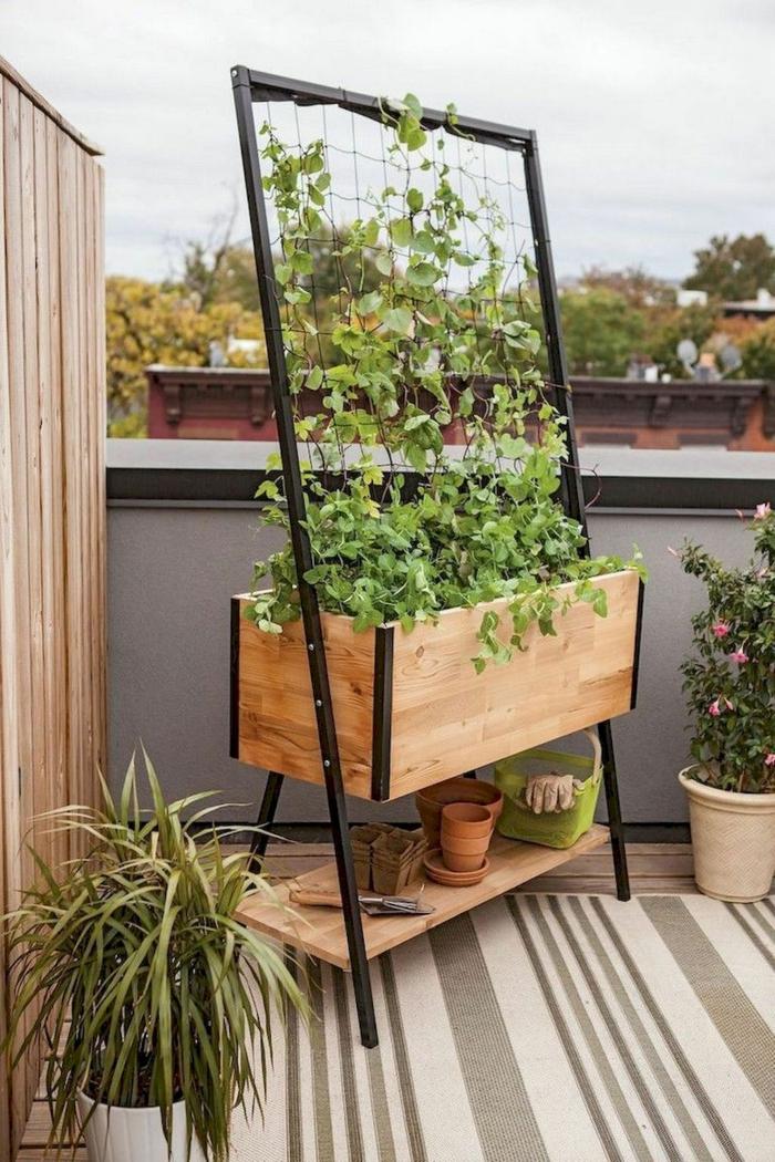Gartendeko aus Holz, Pflanzengefäß für eine Gemüsegarten, Teppich in verschidene Nuancen von hellbraun, Töpfe mit Blumen