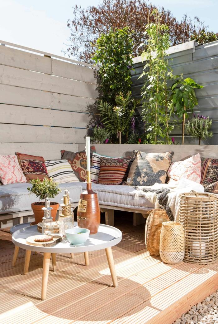 Einrichtung eines Gartens im bohemischen Stil, Sichtschutz aus Holz und grünen Pflanzen, Ecksofa mit vielen bunten Kissen, kleiner runder Kaffeetisch, pinterest Garten