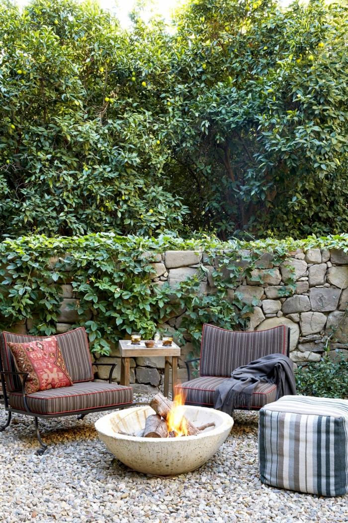 Garten Einrichtung mit einer Feuerstelle aus stein, pinterest Garten, Sichtschutz aus Steinen, zwei dunkelbraune Sessel, große Bäume