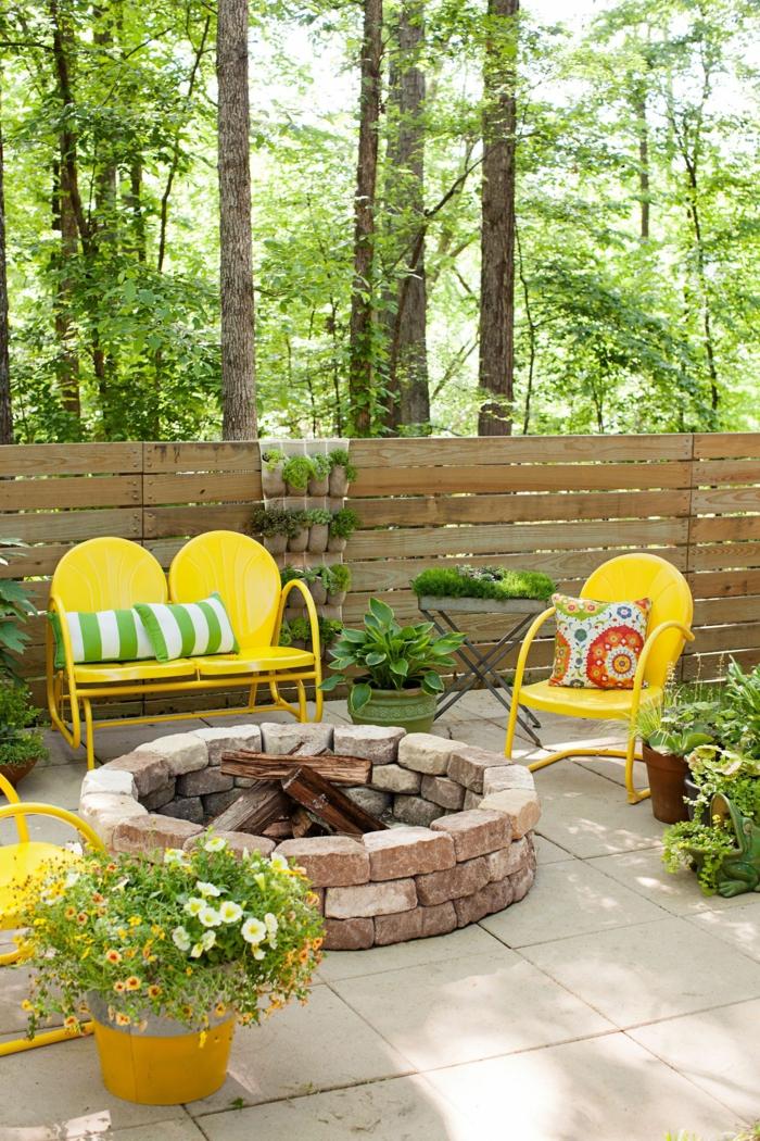 drei gelbe Stühle, Feuerstelle aus Steil, Sichtschutz garten ideen selber machen, gartendeko aus Holz, große Bäume