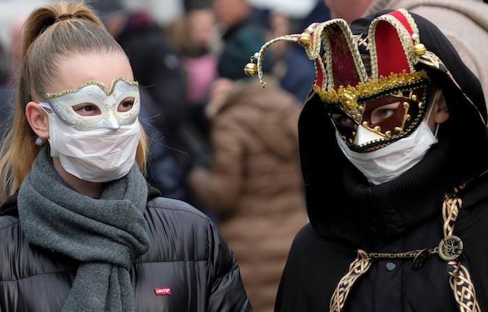 mann und frau mit masken, der diesjährige karneval in venedig soll wegen coronavirus abgesagt werden, drau mit blondem haar und einer weißen maske