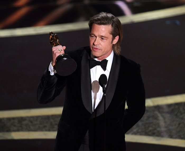 ein mann mit weißem hemd und mit schwarzer fliege, der schauspieler brad pitt mit einem goldenen oscar preis