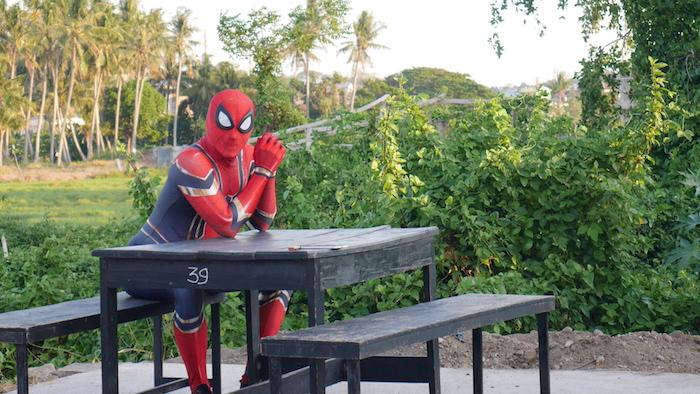 ein wald mit palmen, rudi hartono mit einem kostüm von spiderman, ein schwarzer tisch aus holz, die insel sulawesi