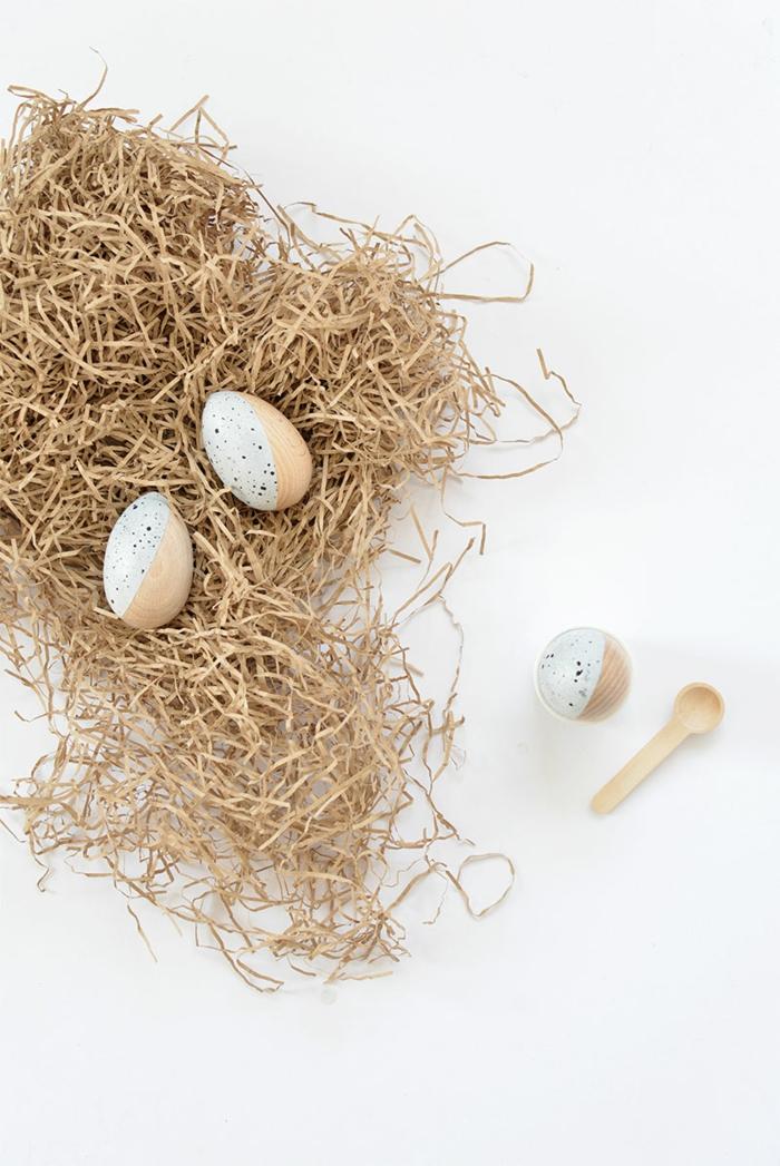 Osterdeko Holz, minimalistische Ostereier aus Holz bemalt in Acrylfarbe, Eier gelegt auf künstlichem Heu, kleiner Holzlöffel