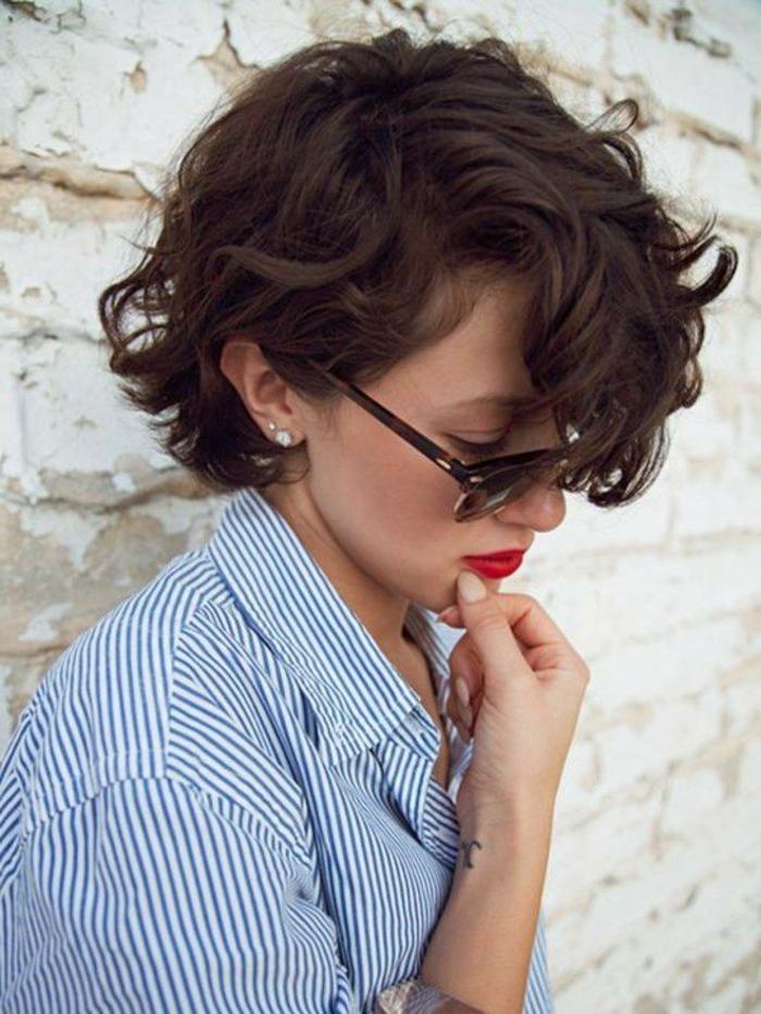 Kurzhaarfrisuren Damen Bilder, braune Haare mit Locken, runde Sonnenbrillen in schwarz, roter Lippenstift, weiß blaue Bluse gestrift