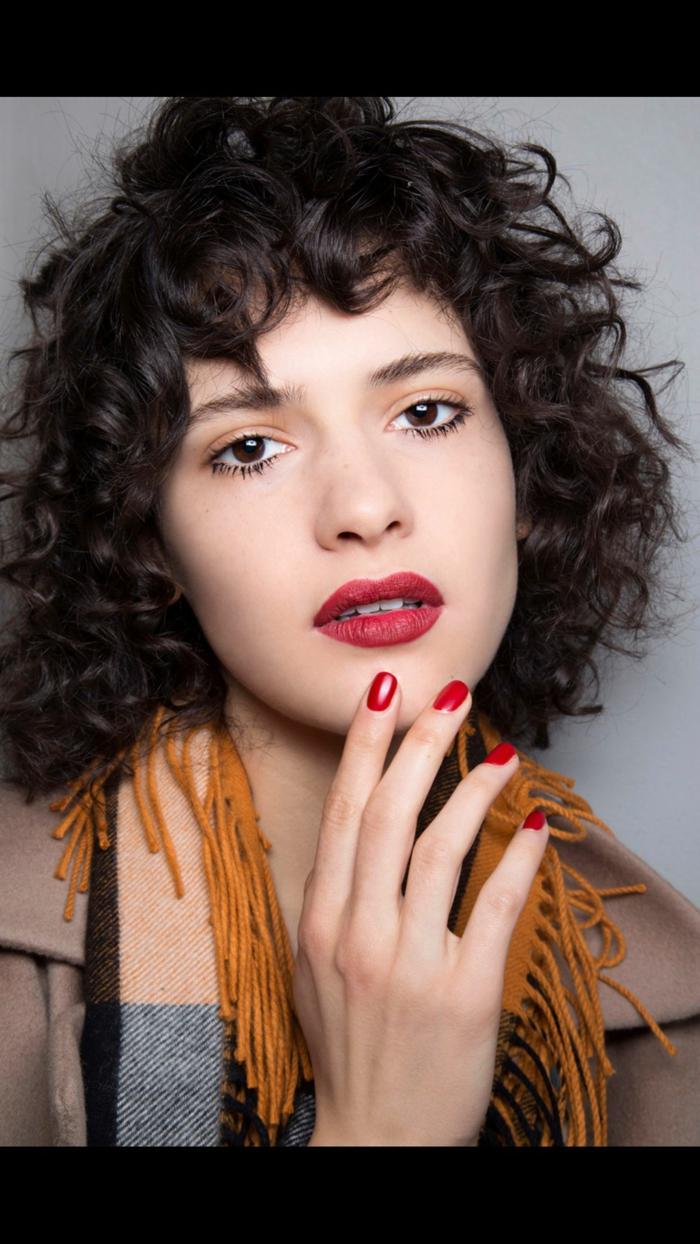Fotoshooting Nahaufnahme eines Models, knallroter Lippenstift und Nagellack, bunter Schal, Frisuren Locken kurz