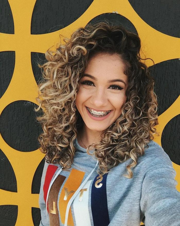Lächelndes junges Mädchen mit Zahnspange, Naturlocken Frisuren mit blonden Strähnen, Bluse in grau mit Abdruck