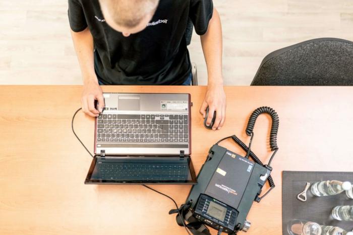 Prüfung ortsveränderlicher elektrischer Betriebsmittel, DGUV V3 Vorschrift, Mann prüft Laptop mit einem Gerät